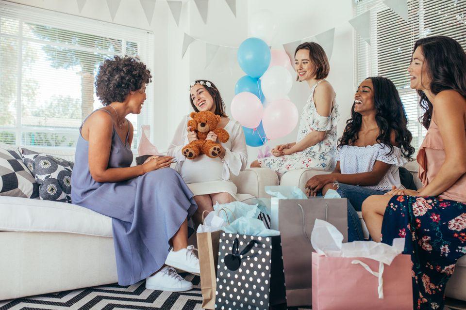 Babyshower: Schwangere sitzt mit Freundinnen zusammen und feiert.