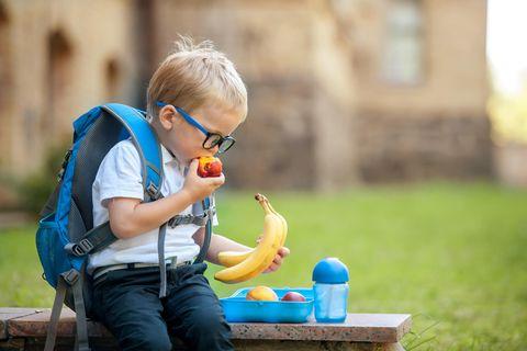 Ein Junge sitzt auf einer Bank und packt seine Brotdose aus.