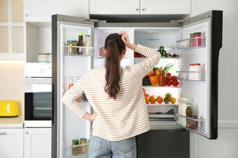 Eine Frau steht vor dem offenen Kühlschrank und kratzt sich am Kopf