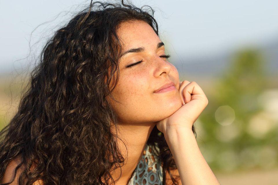 Horoskop ab 17.9.2021: Frau genießt mit geschlossenen Augen die Sonne
