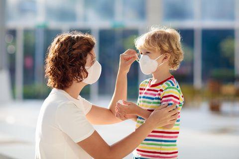 Eine Frau zieht einem Jungen eine Maske auf.