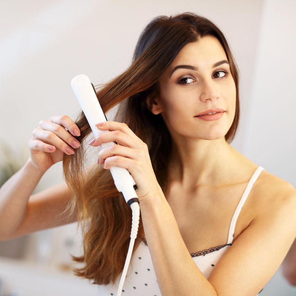 Frau mit Glätteisen, Haare glätten