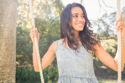 Horoskop: Schwarzhaarige Frau lacht glücklich auf einer Schaukel