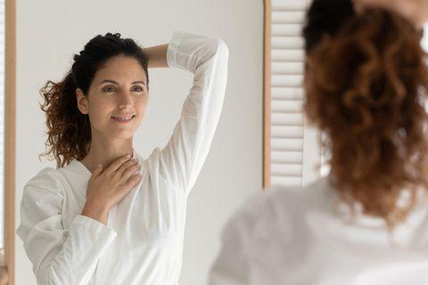 Glücklich auf dem Mittelweg: Zufriedene Frau sieht sich im Spiegel an