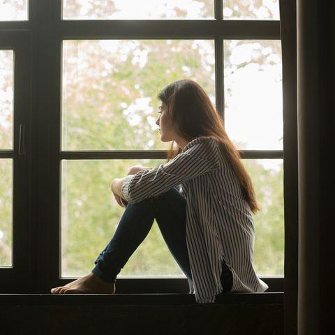 Gedankenkarussell stoppen: Frau schaut nachdenklich aus dem Fenster