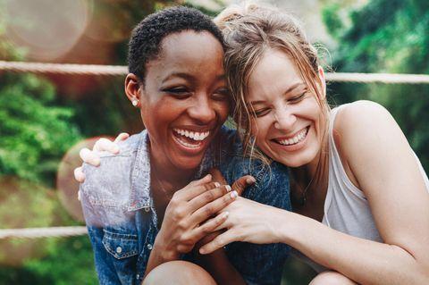 Wahre Liebe finden: Zwei verliebte Frauen lachen glücklich zusammen