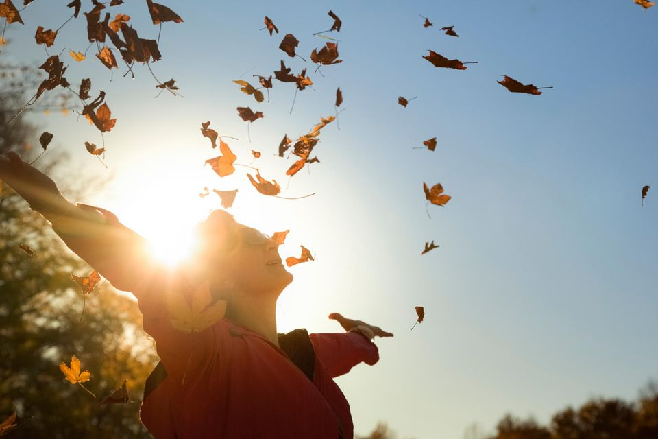 Frau wirft Herbstlaub in Luft