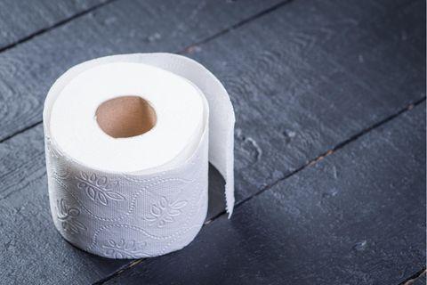 10 Fakten über Toilettenpapier: Eine Rolle Toilettenpapier auf einem schwarzen Tisch.