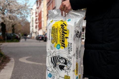 Goldeimer: Frau trägt ein Paket Toilettenpapier