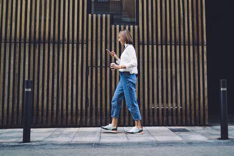 Gehstil + Persönlichkeit: Frau geht auf dem Bürgersteig.