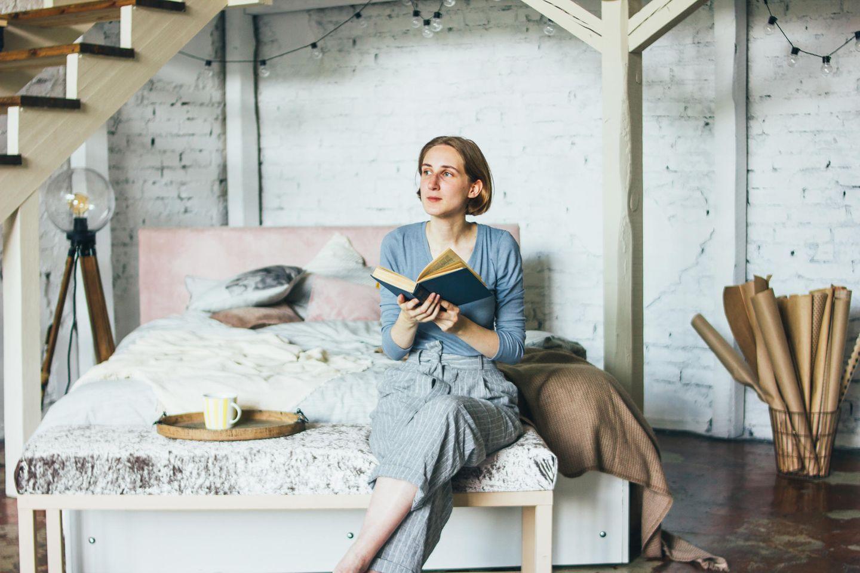 Psychologie: Frau sitzt nachdenklich auf dem Bett
