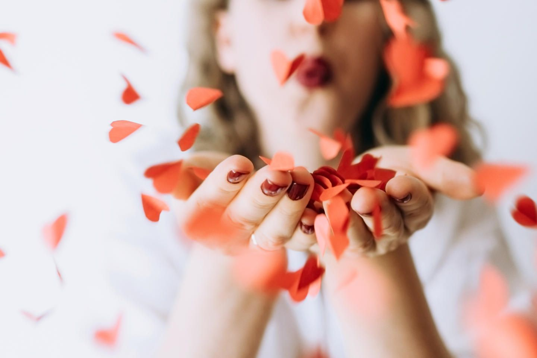 Liebe neu gedacht: Frau pustet Rosenblätter in die Kamera