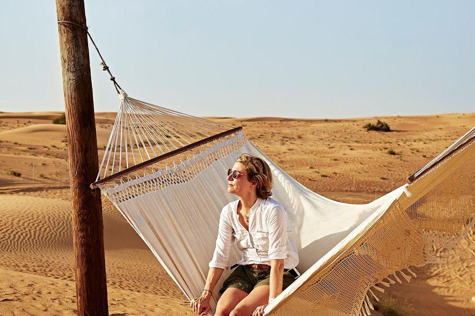 Dubai: Frau auf einer Hängematte in der Wüste