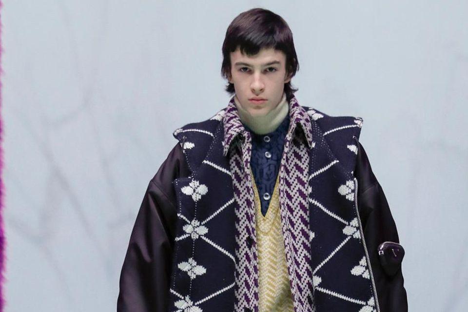 Man kennt es schon: Prominente Töchter und Söhne starten eine internationale Model-Karriere. So auch in diesem Fall: DiesenSprössling hatten wir bislang so gar nicht auf dem Schirm. DunkelbraunePott-Frise, trainierter Körper – und er ist der Star auf dem Laufteg von Prada bei der Mailänder Fashion Week. Na, eine Idee, von welchem Star dieser junge Mann abstammt?