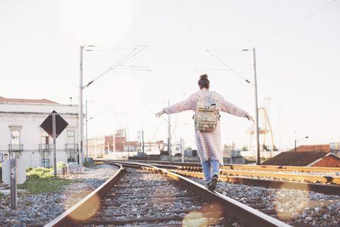 Psychologie: Eine Frau balanciert auf Eisenbahnschienen