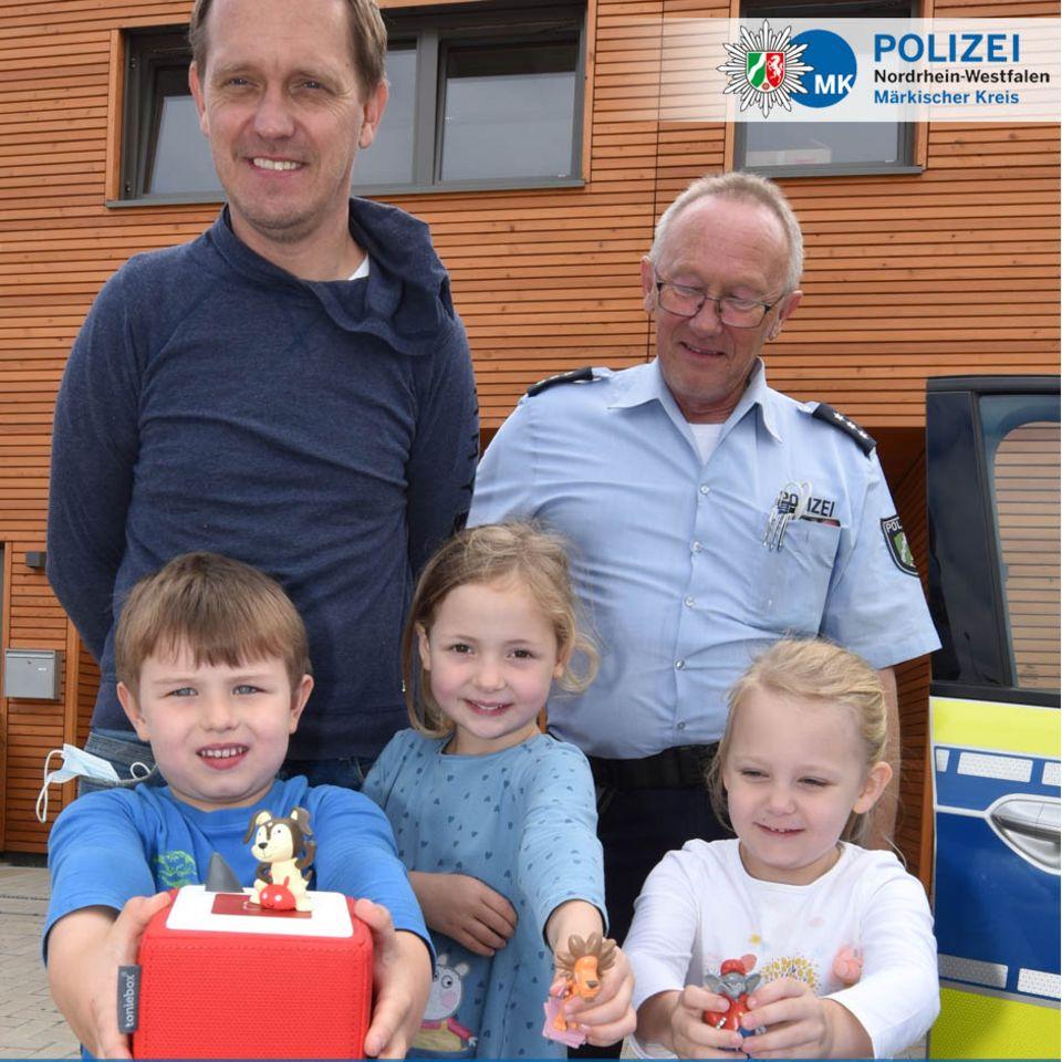 3 Kinder halten eine Toniebox in die Kamera. Ein Polizist und ihr Kindergärtner sind auch fröhlich.