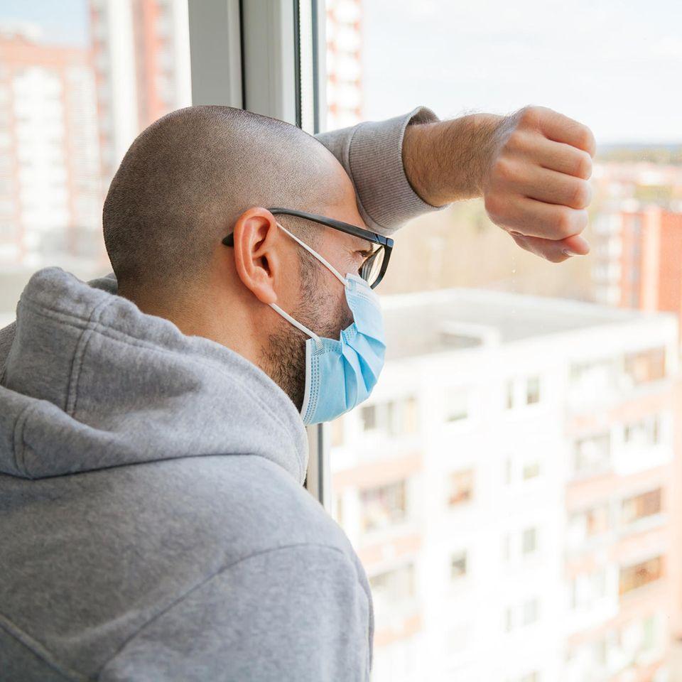 Ein Mann schaut während seiner Quarantäne aus dem Fenster.