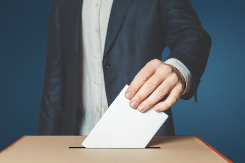Ein Mann steckt seinen Wahlumschlag in die Wahlurne.