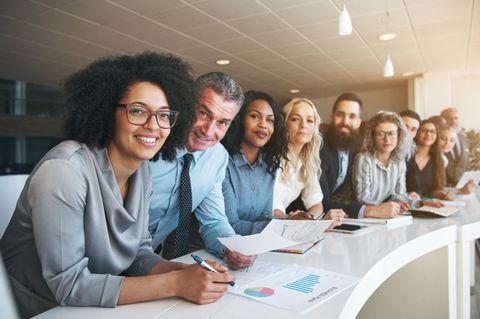 Chancengleichheit im Job: Lächelnde Menschen sitzen an einem Tisch