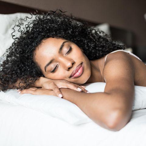 Eine Frau liegt glücklich schlafend in ihrem Bett.