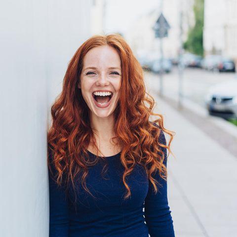 Horoskop: Rothaarige Frau lacht glücklich in die Kamera