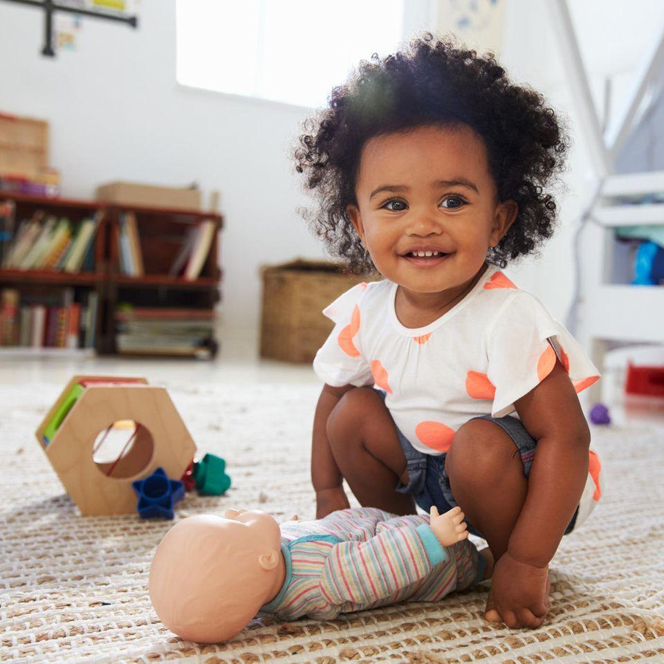 Ein kleines Mädchen hockt in ihrem Zimmer und spielt mit einer Puppe.