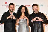 Gemeinsam laufen Moderator Matthias Killing, Sängerin Francisca Urio und Sänger Jay Khan (v.l.n.r.) über den roten Teppich der Charity-Gala. Während sie in die Kameras lächeln, formenalle drei mit ihren Händen ein Herz.
