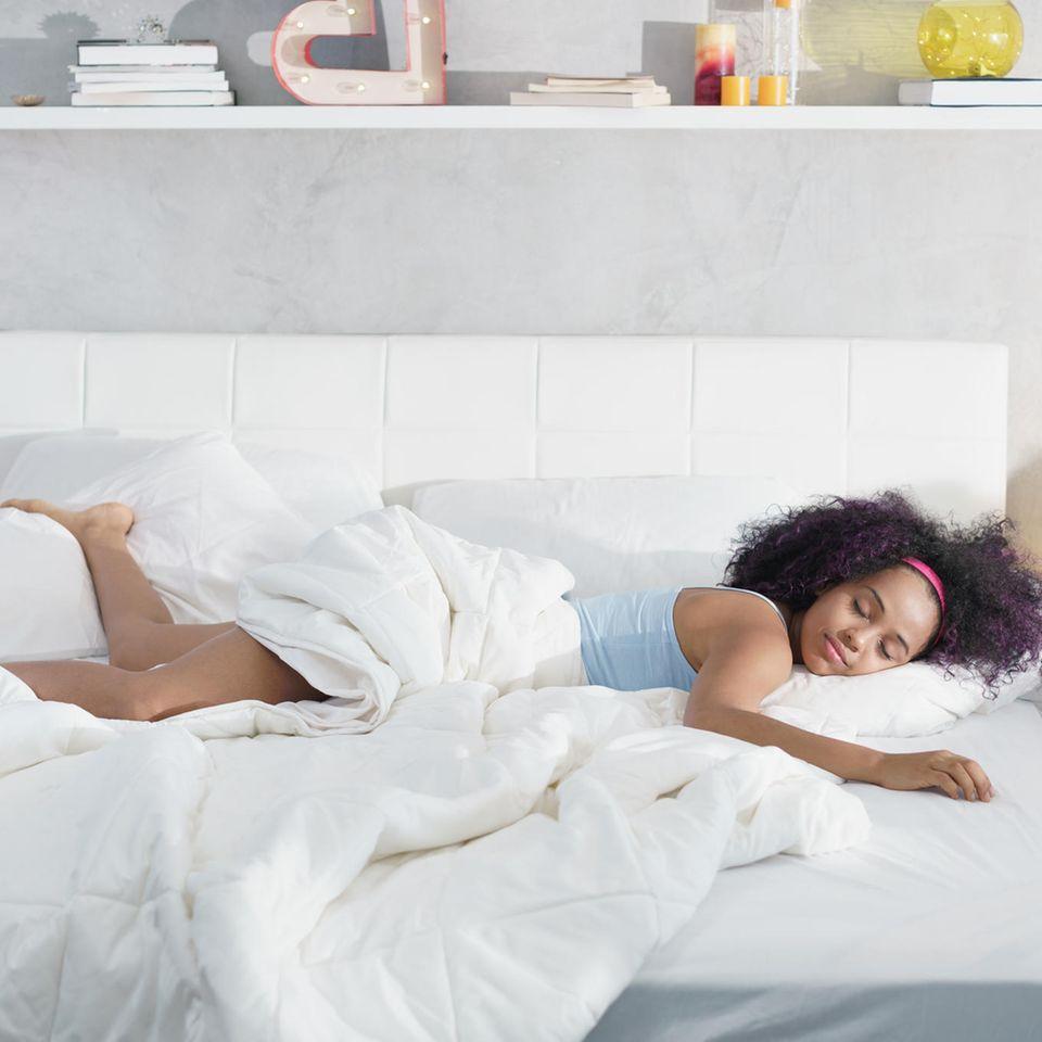 Persönlichkeit: Frau liegt quer im Bett und schläft