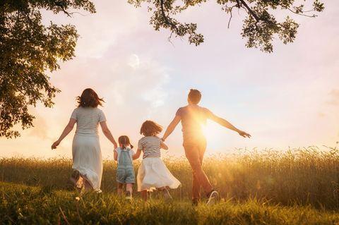 """Projekt """"Corona-Auszeit für Familien"""" gestartet: Eltern mit zwei Töchtern auf einer Wiese"""