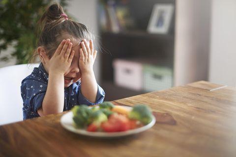 Ein Kind hält sich die Augen zu, während es vor einem Teller Gemüse am Tisch sitzt.