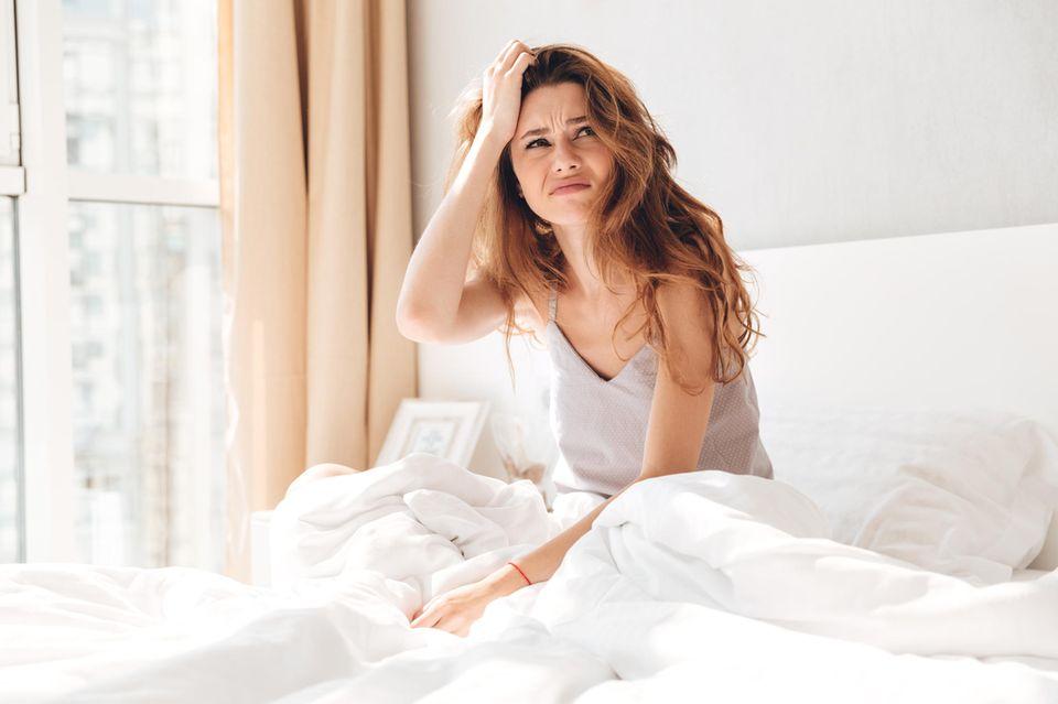 Traum vom Ex: Frau sitzt verwirrt in ihrem Bett und guckt irritiert zur Seite