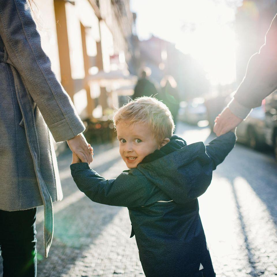 Kleiner Junge hält die Hände seiner Eltern