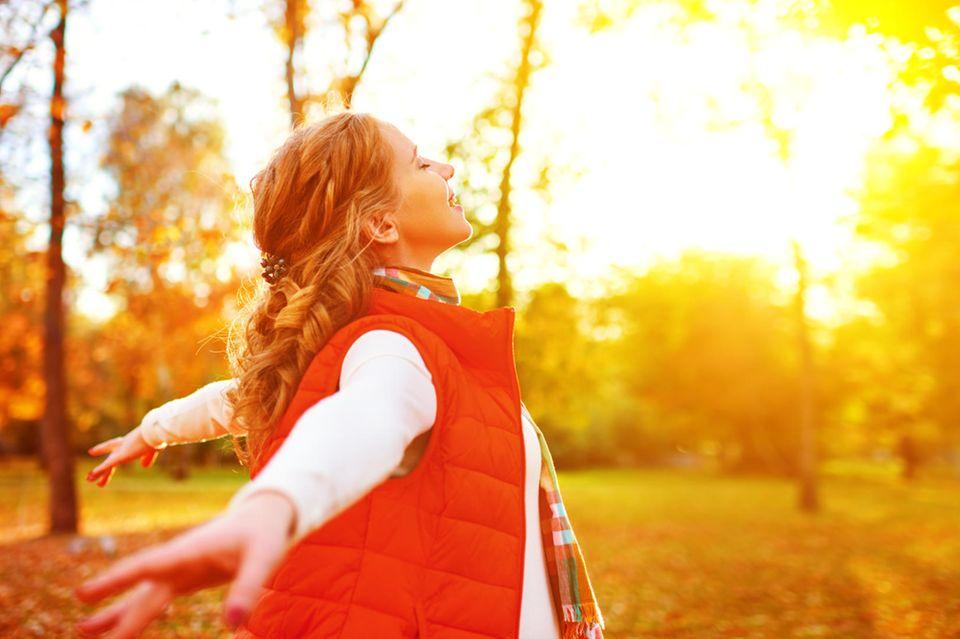 Horoskop ab 1.10.2021: Frau genießt die Herbstsonne