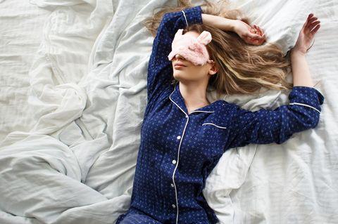 Ab in die Falle: Frau schläft im Pyjama und mit Schlafmaske