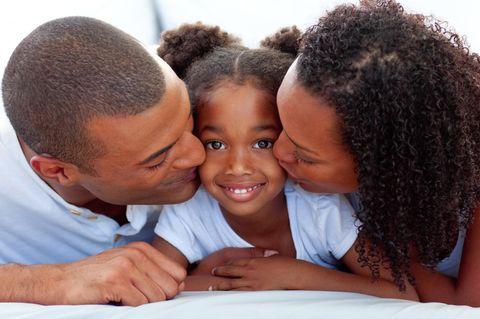 Kinder gegen Rassismus stark machen: Mutter und Vater küssen ihre Tochter auf die Wange