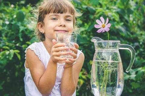 Trinkwasser: Mädchen hält Wasserglas in der Hand