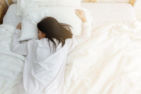 Frau schläft im Bett: Das bedeutet es, wenn du im Traum deinen Partner betrügst