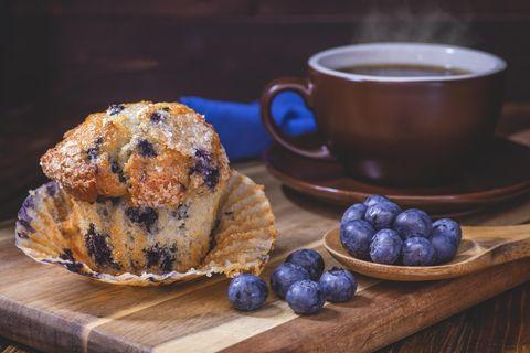 Blaubeer-Muffins mit Blaubeeren in einem Löffel und einer Tasse Kaffee auf einem Holzbrett.