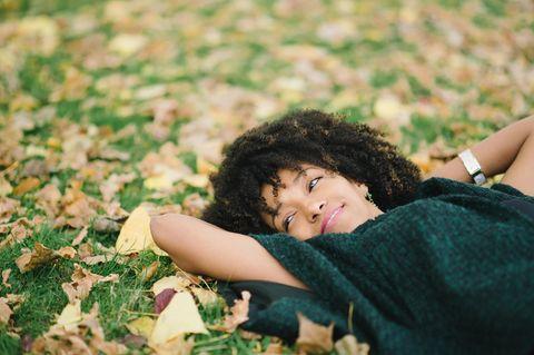 Horoskop: Eine fröhliche Frau auf einer Herbstwiese