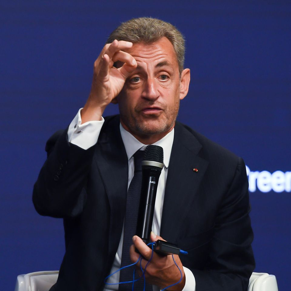 Nicolas Sarkozy auf einer Bühne mit Mikrofon in der Hand
