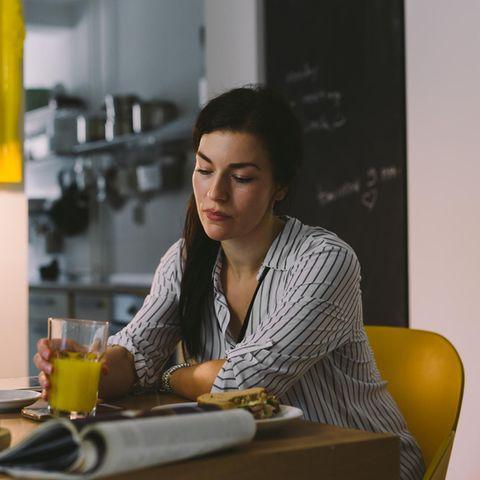 Insulinresistenz: Frau sitzt mit Essen nachdenklich am Tisch
