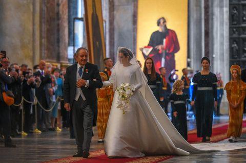 Victoria Romanowna Bettarini schreitet an der Seite ihres Vaters zum Altar.