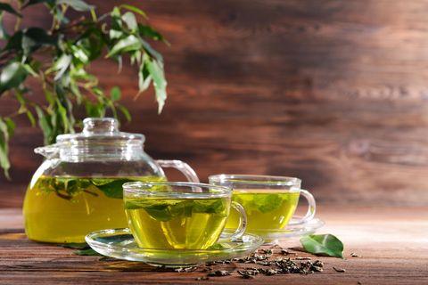 Grüner Tee: Glasbecher und Glaskanne mit gesundem grünen Tee