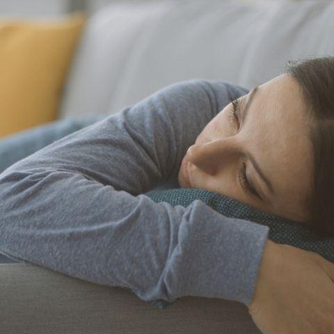 Stellvertreter-Burnout: Frau auf dem Sofa, starrt müde in die Luft