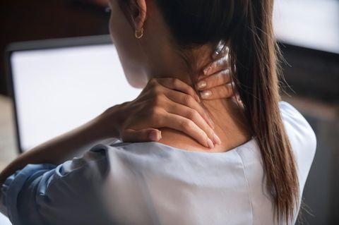 Verspannter Nacken: Frau massiert Genick vor Computer