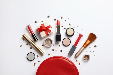 Vor einem Make-up Täschchen liegen Make-up-Produkte, ein Geschenk und Sternchen Dekoration.