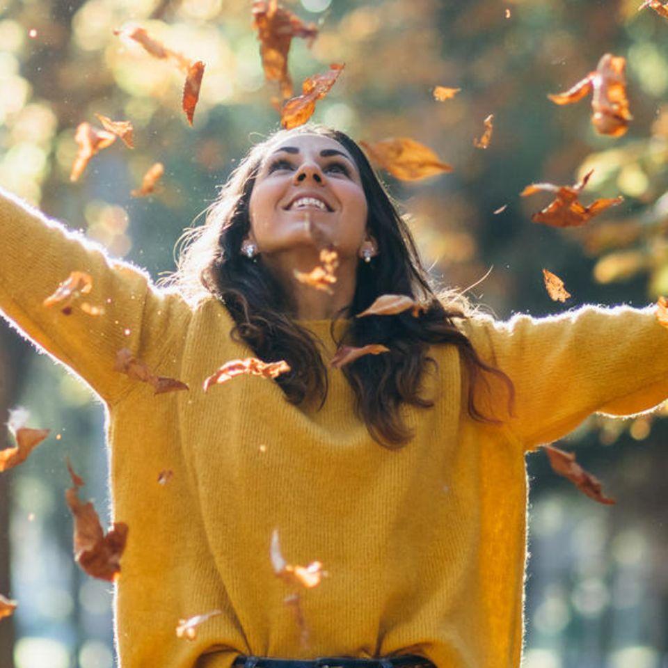 Eine Frau steht im Blätterregen im Wald.