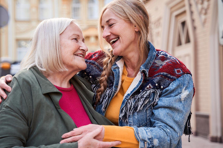 Klammernde Mütter: Mutter und Tochter umarmen sich lachend
