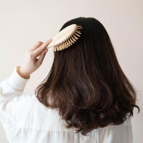 Die richtige Haarepflege: Frau bürstet ihre Haare