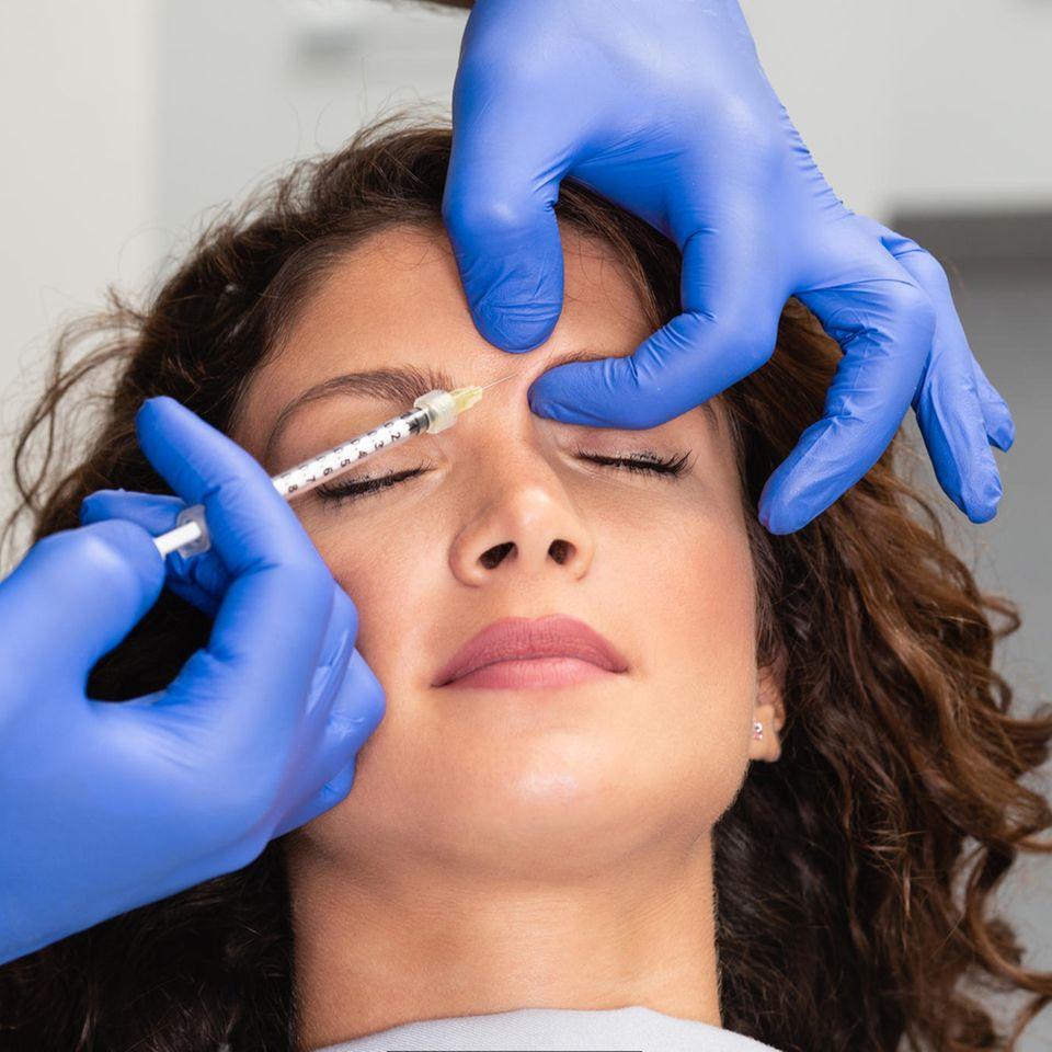 Baby Botox: Ein Arzt spritzt einer Frau eine Dosis Baby Botox zwischen die Augenbrauen
